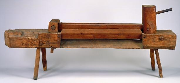 19th-century flax break: a large beam sitting on four legs with another piece of wood on top.